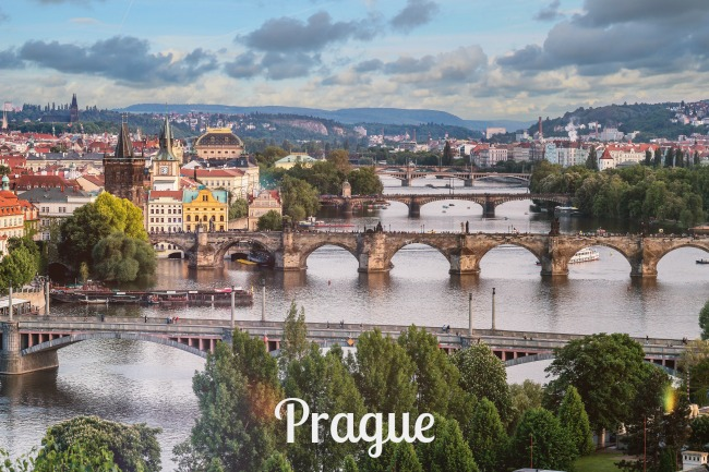 Looking down the river in Prague. 4 bridges with large arches span the river. There are buildings and trees on both sides of the river and hills can be seen in the distance.