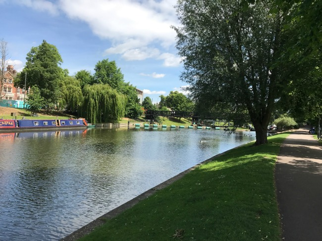 Standing on the bank of a river in Cambridge. There is a colourful barge moored on the opposite bank and small boats can be seen further down. Large trees line the river and a building can be seen in the distance.