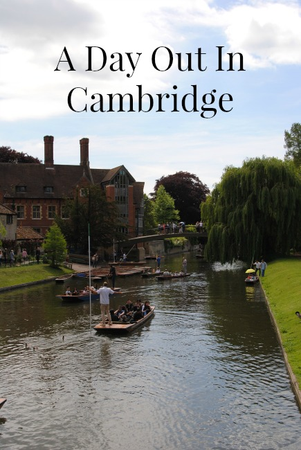 Several punting boats full of passengers on the River Cam in Cambridge.