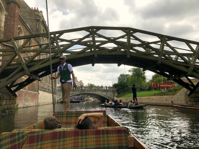 Looking at Mathematical Bridge over the River Cam in Cambridge from one of the punting boats. Two people are sitting at the front of the boat on tartan covered chairs, and the punter is facing towards the camera with his back to the bridge and a long pole in his hand, used to manoeuvre the boat. Another bridge and boat can be seen further down river.