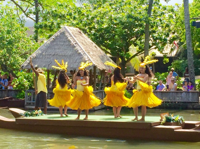 Ladies in traditional Polynesian dress dancing on a barge. There is a crowd of people lining the bank of the canal watching them .