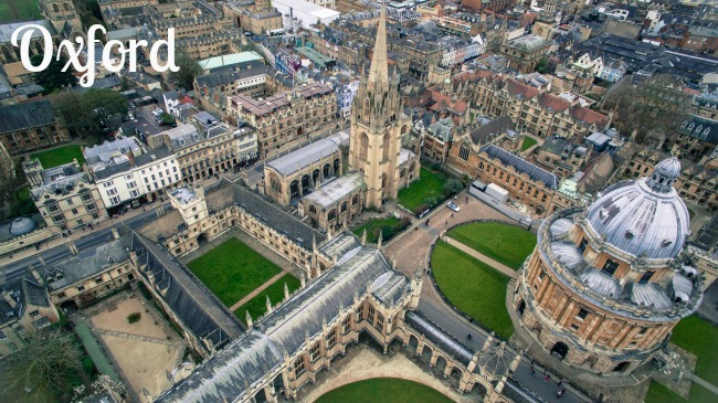 Looking down into the grounds of one of the Oxford universities. The buildings are set out in a grid pattern with large grass areas between them. Tall spires from the buildings reach up into the sky.