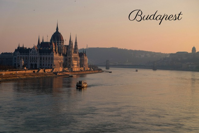 A view of the Danube river. A small boat is floating past a grand palace.