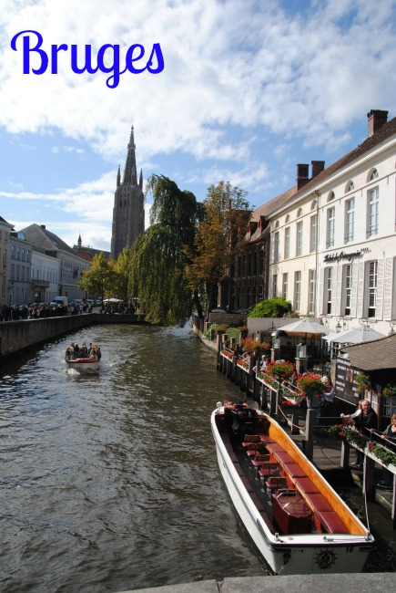 A canal in Bruges with a few boats on it. Buildings line both sides of the canal and trees overhang the water in the distance.