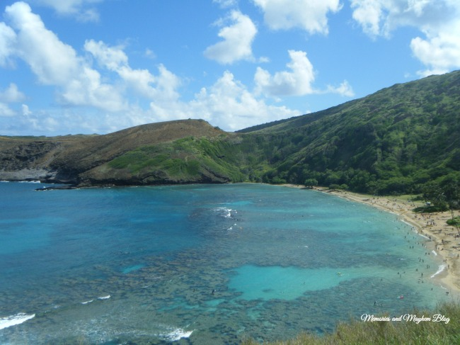 Hanauma Bay in Oahu. The coral reefs can be seen just below the surface of the ocean. The mountains are covered in greenery and rise up behind the beach.