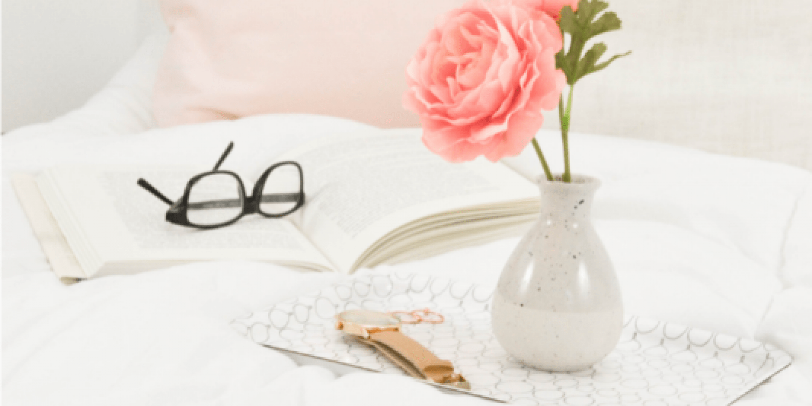 A small bunch of pink flowers and a pair of glasses resting on a book